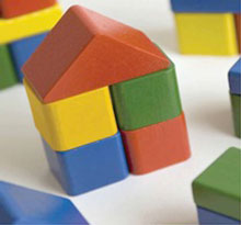 toy house built out of multi coloured and shaped wooden blocks